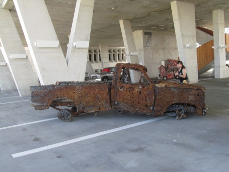 """Here lies the remains of what used to be a truck, but what then became a target for an annual machine-gun festival in Kentucky. Now you know that type of festival exists. (Lucien Smith, """"The sound of the engine still running and for the last time they locked eyes, together again in the end,"""" 2013.)"""