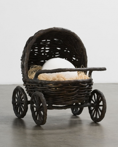 sculpture of a baby stroller with an egg by liz craft