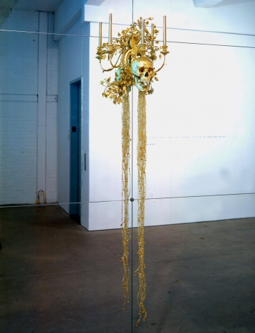 gold skull mounted on a mirror by angelo filomeno