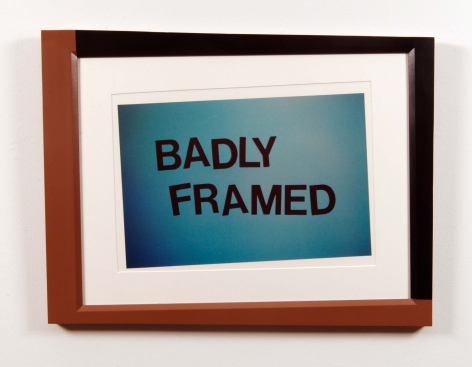"crookedly framed image reading ""badly framed"" by john waters"