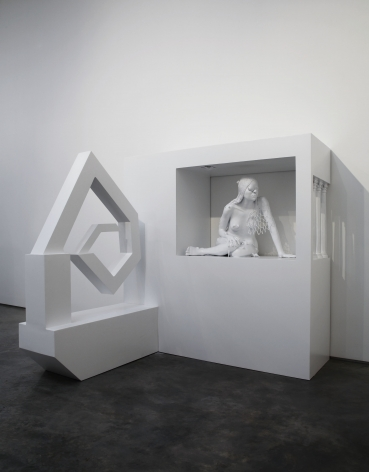 sculpture of a woman crouching in an enclosure by liz craft
