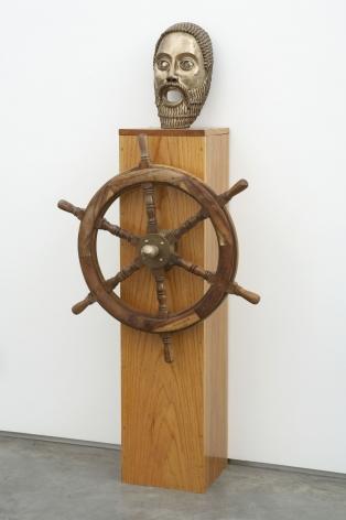 sculpture with wheel and mask on wooden pedestal by pentti monkkonen
