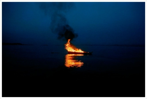 a photograph from video art by thiago rocha pitta showing a boat on fire in the water