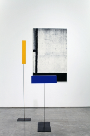 installation by melissa gordon with black and white grid painting and blue and yellow rectangular sculptures