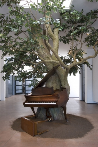 An installation of a piano and a steel sculpture tree created by the artist Sanford Biggers