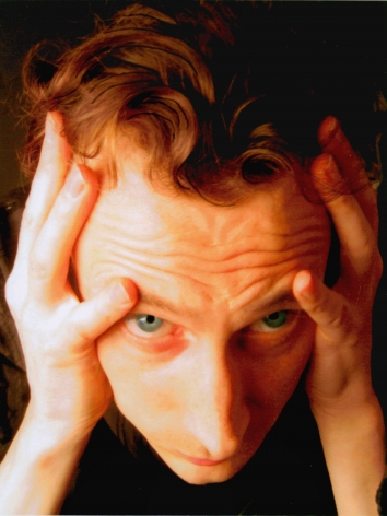photograph of a man clutching his temples by jeffrey wells