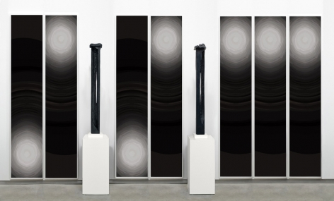 arrangement by anthony pearson with two black rectangular sculptures and six paintings