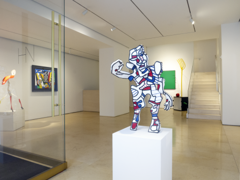Installation view of Masterworks. View of the lobby entrance featuring a medium size sculpture by French sculptor, painter Jean Dubuffet. The sculpture is titled (The Welcomin) L'Acceuillant and was made in 1973. It represents a human shape standing and waiving with its right arm. The sculpture is overall white but is covered with thick blacl lines, red and blue spots and stripes that define in a simple way the face of this figure. This style is the famous Hourloupe signature style that Dubuffet used in many of his paintings and sculptures.
