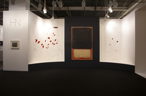 Installation view of Art Basel   Basel 2019, booth H5. ©Helly Nahmad Gallery NY. Photography by Studio MDA. This photo features the inside of the booth, A latge scale painting by Mark Rothko is in the center, two Calder mobile are suspended from the ceiling on each side. On the left side we can see a small painting by Joan Miro hung on the wall.