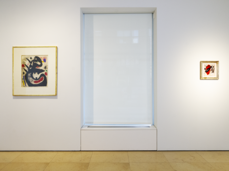 Installation view of Masterworks. This image features two watercolors by Joan Miro the Spanish painter. On the left a medium size watercolors represent a large head painted in black with a mouth open wide and a lively expression. On the right ot os the cover of a poetry magazine, representing a black fish over. a red spot.