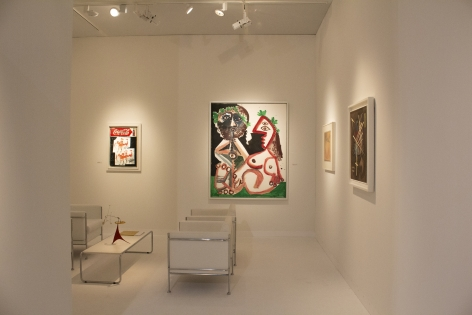Installation view of Art Basel   Basel 2019, booth H5. ©Helly Nahmad Gallery NY. Photography by Studio MDA. This photo features the inside of the booth, we can see a painting by Picasso on the left a small painting by basquiat and on the table a small mobile by Alexander Calder.