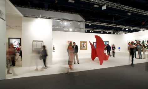 Installation view of Art Basel | Miami Beach 2013, booth B01. This photo depicts the booth from far and the gallery staff and visitors looking at a few paintings and walking around the red large scale Alexander Calder sculpture called Brontosaurus. Photography by Karen Fuchs.  © 2018 Calder Foundation, New York / Artist Right Society (ARS), New York. ©Helly Nahmad Gallery NY.