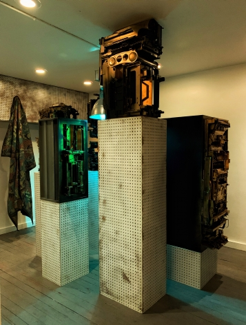 Upstairs exhibition room - Exhibiting five assemblage sculptures on pegboard pedestals- various sizes.  Sculptures were placed surrounding a condensed 400-watt sulfur lamp, low hanging with a loud buzzing sound.