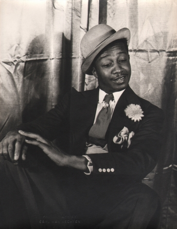 Carl Van Vechten, Avon Long as Sporting Life, Porgy & Bess, ​1942. Subject in a seated pose with legs crossed and hands on knee, looking down and to the right.