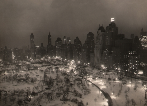 """Paul J. Woolf, Central Park Looking Southeast, c. 1935. Night time cityscape showing the southeast corner of the park occupying the lower third of the frame with tall buildings, including """"Essex House,"""" surrounding."""