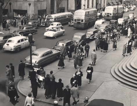 08. Simpson Kalisher, Untitled, c. 1949. Many pedestrians walking on a street corner from a slightly elevated view. Cars and double-decker busses can be seen on the street.