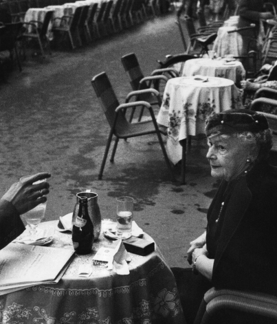 Piergiorgio Branzi, Roma, Via Veneto, ​1959. An older woman seated at the foremost of a row of tables. A hand holding a glass is extended towards her from outside the left of the frame.