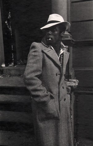 09. Anthony Barboza, Harlem, NY, ​1970. A man standing on the sidewalk with hands in a long coat. He wears a white hat, body facing the right with his face turned left.