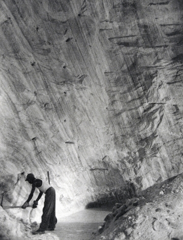 Harold Haliday Costain, Clearing the Path Along the Base of the Cliff, The Great Avery Island Salt Mine, 1934. A worker wields a pickaxe in the lower left corner of the frame.