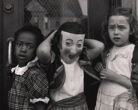 Marvin E. Newman, Chicago, ​1950. Three young girls stand against a door, one wearing a mask.