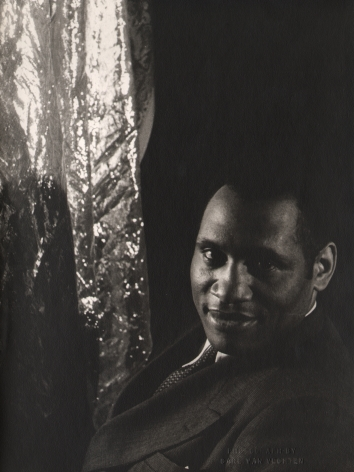 Carl Van Vechten, Paul Robeson, 1933. Subject smiles to the camera with torso facing left, a reflective material hangs to the left of the frame.