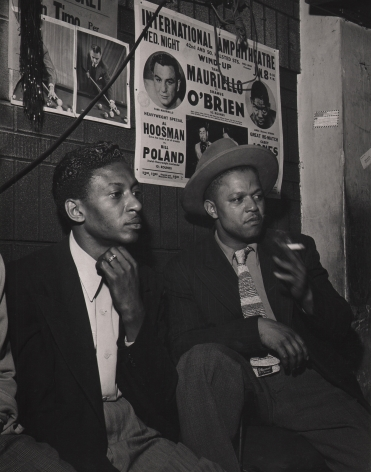Wayne Miller, Spectators at Pool Hall, Chicago, ​1946–1947. Two men seated against a brick wall with posters on it, both looking to the right. One man holds a cigarette.