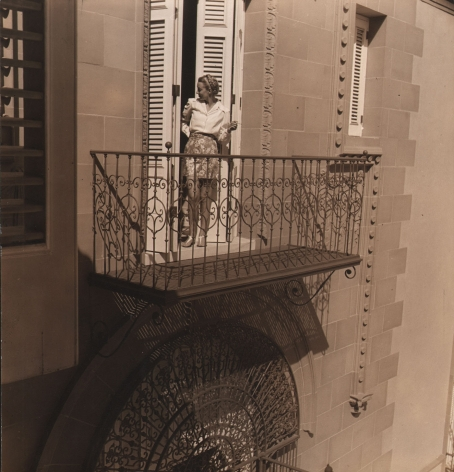 Louise Dahl-Wolfe, Morning in Havana, ​1941. A model stands in the doorway to a balcony, looking back into the interior.
