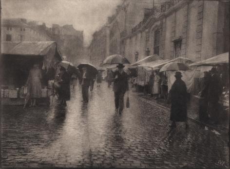 04. Léonard Misonne, Untitled, c. 1930. Figures with umbrellas walk a wet, cobbled market street. Sepia-toned print.