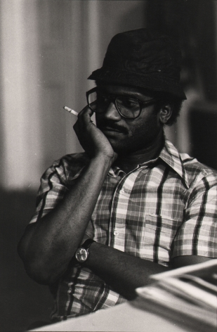 03. Anthony Barboza, Beuford Smith, First Black Photographers Annual Meeting, NYC, 1970s. Torso of a seated man in a checked shirt wearing glasses and a hat, one hand held to his face.