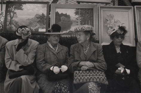 Bob Hollingsworth, Open Air Art Show, Union Square, San Francisco, 1949. Four older women, purses in their laps, sit beneath a metal fence covered in framed landscape and still life paintings.