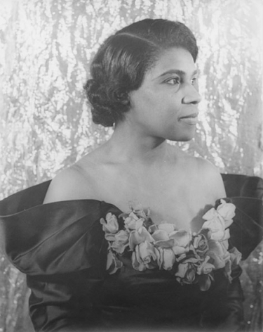 10. Carl Van Vechten, Marian Anderson, 1940. Bust-length portrait with subject in an off-shoulder floral gown in partial profile facing the right of the frame.