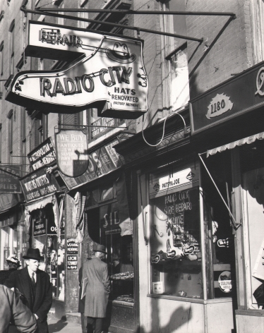 """3. Todd Webb, Rockefeller Center, New York City. Shops on Sixth Avenue near Rockefeller Center, 1947. Street scene featuring a shoe-shaped neon sign for """"Radio City Hats"""" in the upper left of the frame."""