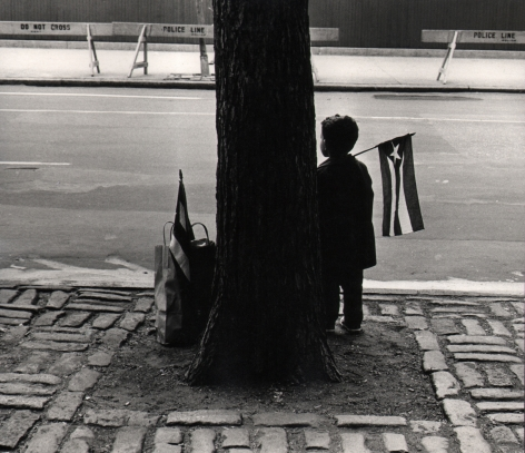 10. Beuford Smith, Boy Holding Flag, 1966. A young boy stands silhouetted beside a tree trunk, facing the street, a small Puerto Rican flag over his shoulder.