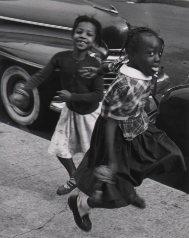 Marvin E. Newman, Chicago, ​1950. Two young girls play on the sidewalk, blurred with motion, smiling at the camera.