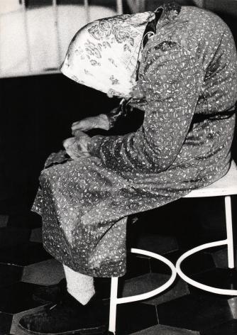 02. Mario Giacomelli, Verrà la morte e avrà i tuoi occhi, 1966–1968. High contrast image. Side profile of a hunched old woman on a white stool.