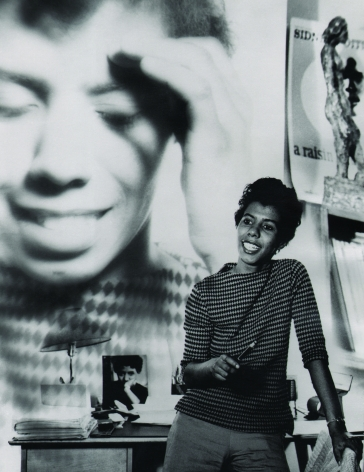 05. David Attie, Lorraine Hansberry at her Bleecker Street apartment, 1959. Subject poses leaning against a desk with a close-up photograph of herself superimposed on the wall in the background.