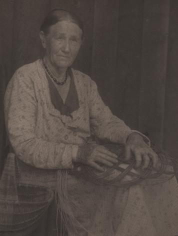 09. Doris Ulmann, Untitled (Basket weaver), 1928–1934. Seated woman weaving a basket in her lap.