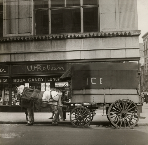 "Cecil Beaton, New York, ​c. 1935. A horse-drawn carriage marked ""Ice"" on the street in front of a building marked ""Whelan Soda Candy Lunch"""