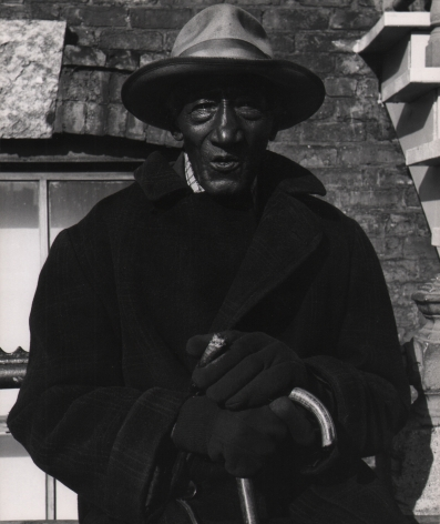 Marvin E. Newman, Chicago, ​1950. An older man in a hat, coat, and gloves holds a cane and a cigar, looking into the camera.