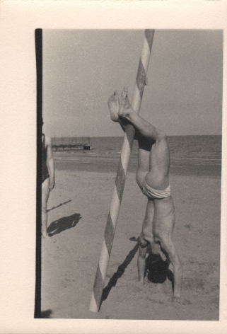 PaJaMa, Untitled, c. 1945. A man in a swimsuit on the beach does a handstand with legs against a striped pole.