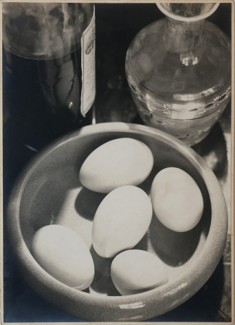 Daniel Masclet, Nature Morte, c. 1926. Looking down on a surface with a ceramic bowl of five eggs, a bottle of liquor, and a glass decanter.
