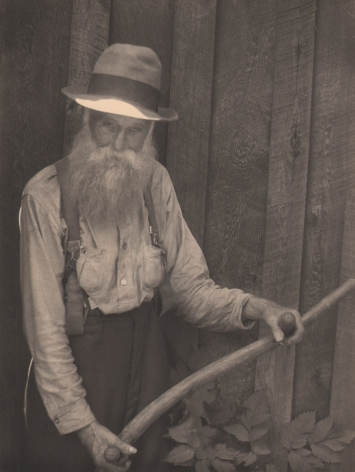 Doris Ulmann, Untitled (Farmer holding oxen yoke), ​1928–1934. Older bearded man in a hat standing against a wooden wall and suspenders holding a wooden rod with two handles.