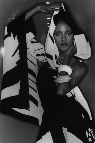 04. Anthony Barboza, Toukie Smith, 1980s. Model stands in a draping, graphic, hooded garment with one arm above her head and one raised to her face.