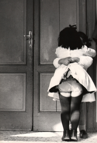 10. Renzo Tortelli, Piccolo Mondo, 1958–1959. High contrast image. Two little girls in white dresses embrace in front of a doorway.