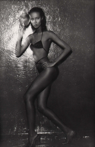 05. Anthony Barboza, Iman, 1970s. Full body portrait against reflective background. Model stands in a swimsuit with one hand at her hip and one holding a mirror to her face.
