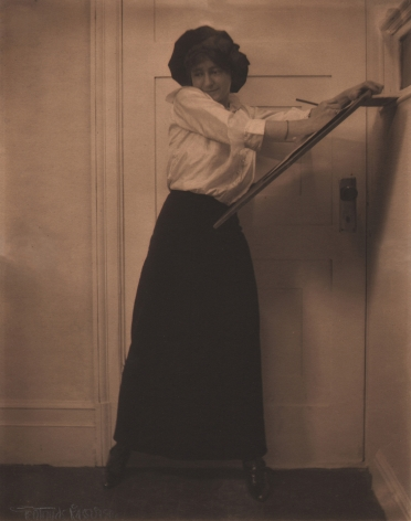 01. Gertrude Käsebier, Untitled, c. 1910. A woman in a white shirt and long black skirt standing in front of a door, seeming to draw against a wooden easel.