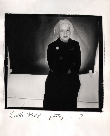 Anthony Barboza, Lisette Model - Photographer, ​1979. Subject stands right-center of the square frame with arms crossed. A black rectangle covers part of the white backdrop.