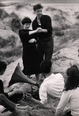 Gianni Berengo-Gardin, Venezia - Il Lido, c. 1958. A group of young adults listens to a record player on the beach. A couple in black is dancing, while the other people are seated in the sand.