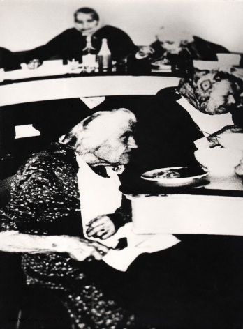 04. Mario Giacomelli, Verrà la morte e avrà i tuoi occhi, 1966–1968. High contrast image. Seated old women eating a meal (two in foreground, two in background).