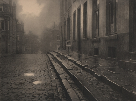 09. Léonard Misonne, [title illegible], c. 1930. Wet, cobbled, residential street and steps in soft light. Sepia-toned print.